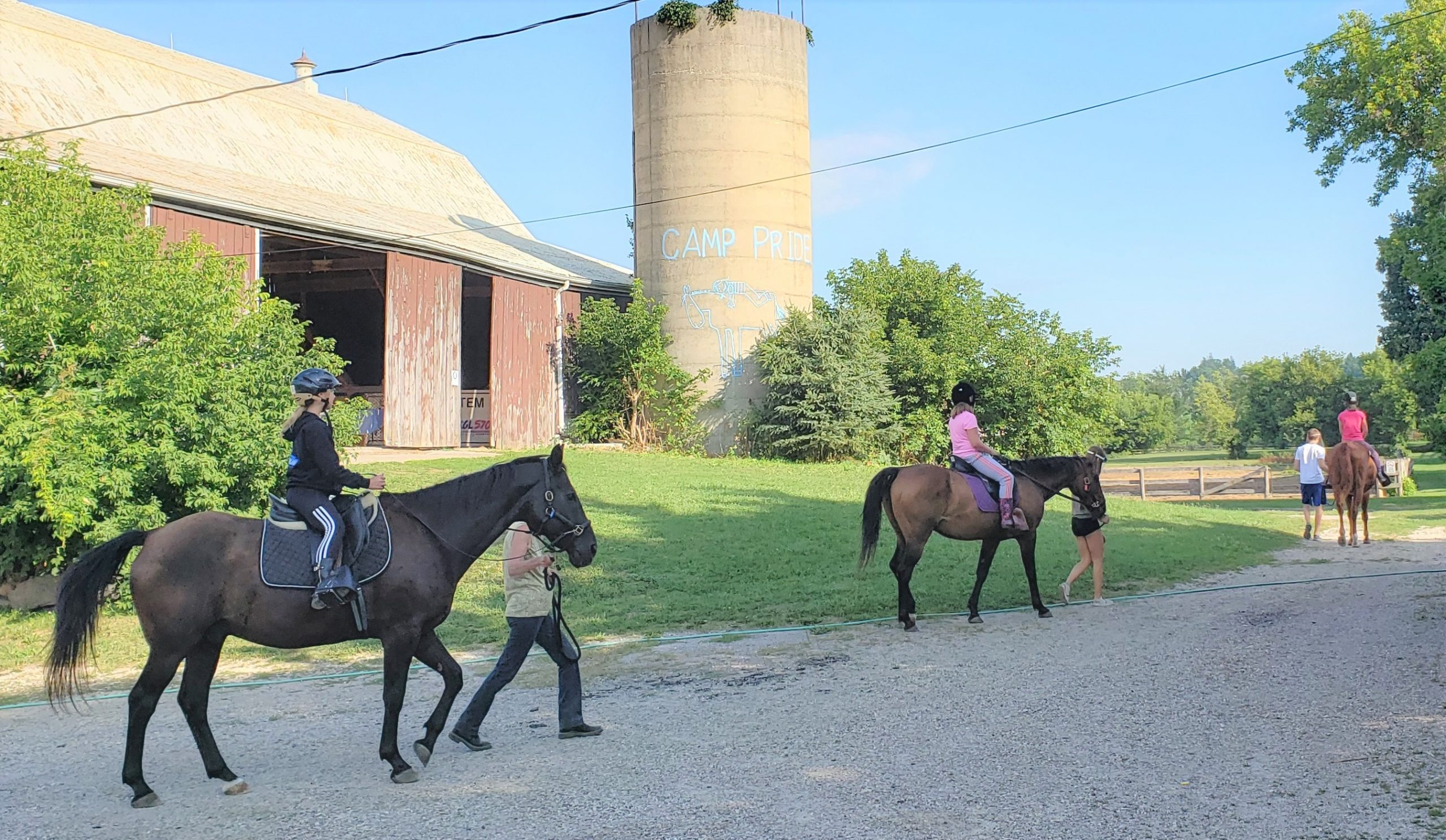campers on horses by the silo